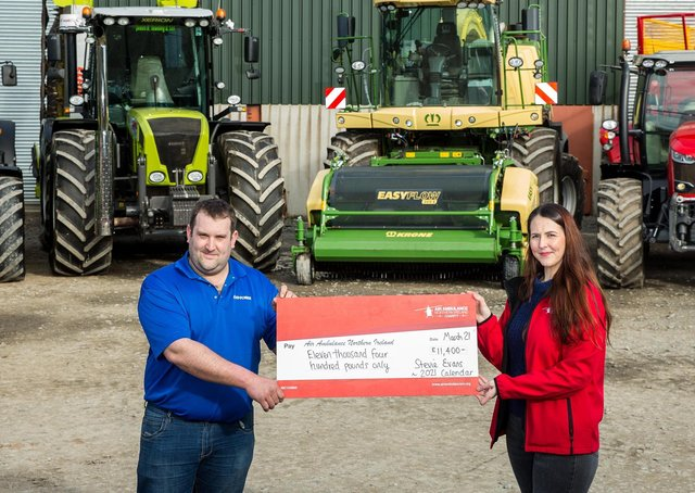 Steven Evans presents Grace Williams, NI Air Ambulance Area Fundraising Manager with a cheque for £11,400 in front of some of the machinery that features in his calendar.