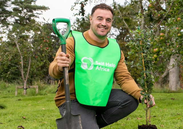 Self Help Africa Northern Ireland Ambassador Rob Herring plants a tree for the charity