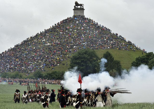People sit on the Lion's Mound, around the lion monument of the Battle of Waterloo during a re-enactment of the 1815 Battle of Waterloo between the French army led by Napoleon and the Allied armies led by the Duke of Wellington and Field-Marshal Blucher, on June 20, 2010, in Waterloo. On June 18, 1815, Napoleon led his 72,000-strong army into battle with 120,000 mostly British and Prussian soldiers on the gently rolling plateau of Waterloo. For a long time the two forces remained in a bloody embrace, but at the end of the afternoon the French emperor's Great Army was routed at the hands of the Duke of Wellington and Field Marshal Bluecher   . AFP PHOTO / GEORGES GOBET (Photo credit should read GEORGES GOBET/AFP via Getty Images)