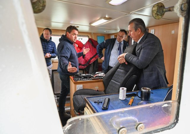 Darren McClements, owner of the fishing vessel Golden Ray, chats with DAERA Minister Edwin Poots about the benefits of the innovative on-board equipment for handling his catch of prawns that he has bought thanks for funding from a DAERA pilot scheme