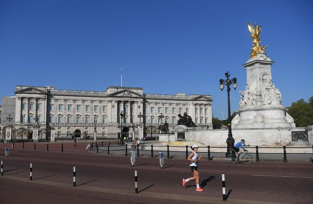 A jogger passes Buckingham Palace; the 40th London Marathon was due to take place this weekend, but has been postponed until October due to coronavirus (Photo: Alex Davidson/Getty Images)